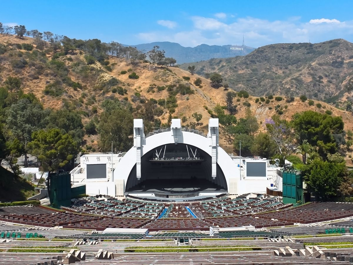 An amphitheater with dozens of rows of seating leading to a large stage covered by a white bandshell