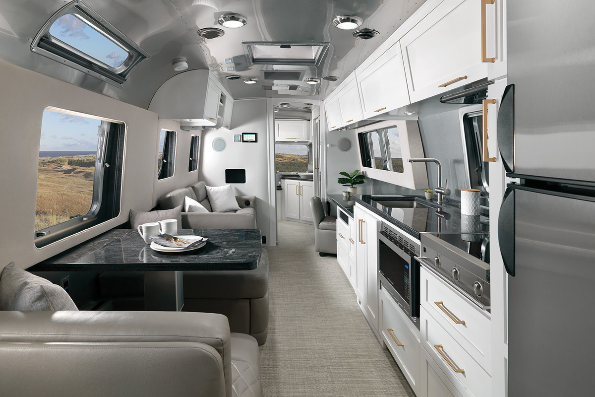 The interior view of an Airstream silver bullet travel trailer. There are white cabinets with brass hardware, a kitchen, and a gray couch.
