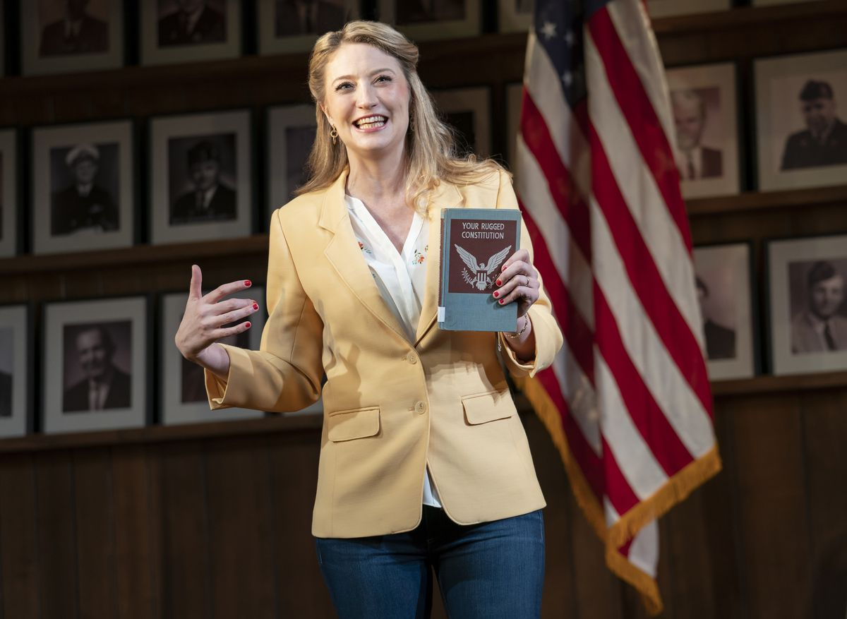 heidi schreck holds up a copy of the constitution