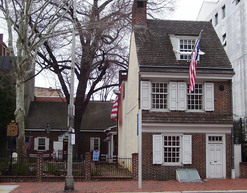 The exterior of the Betsy Ross House. The facade is red brick and there is a grey roof. There are white shutters.