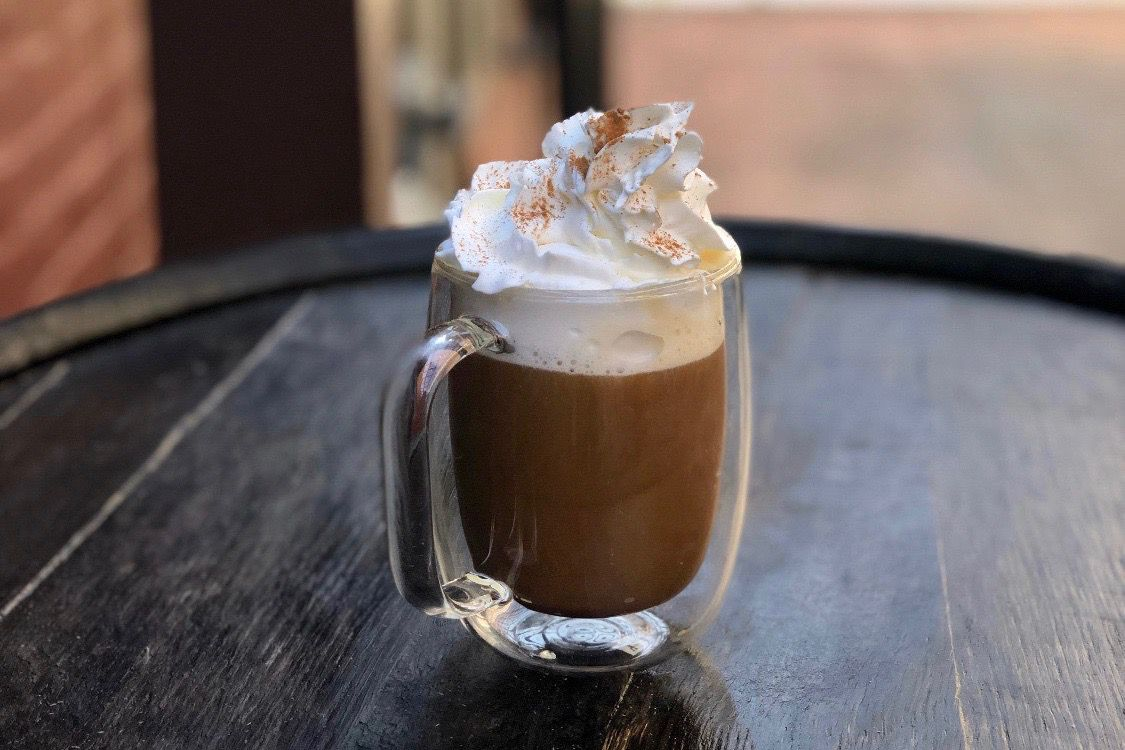 An Irish coffee garnished with a huge dollop of whipped cream sits on top of a wooden barrel.