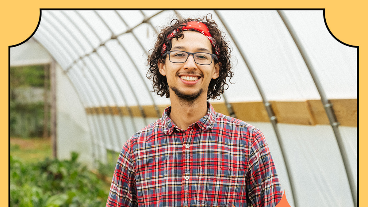 A man stands inside a greenhouse