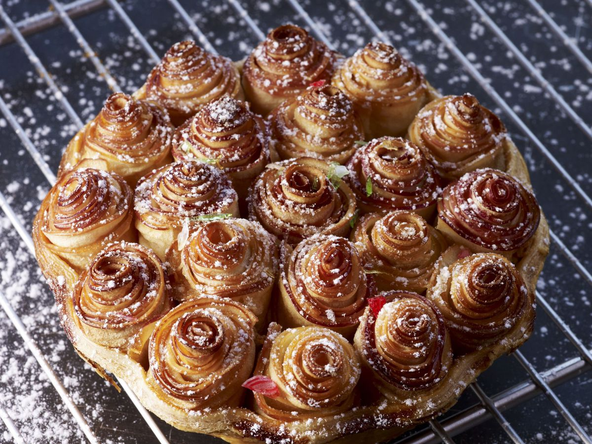 An apple tart, with spiraling toppings that look like a bouquet of flowers, sitting on a wire rack