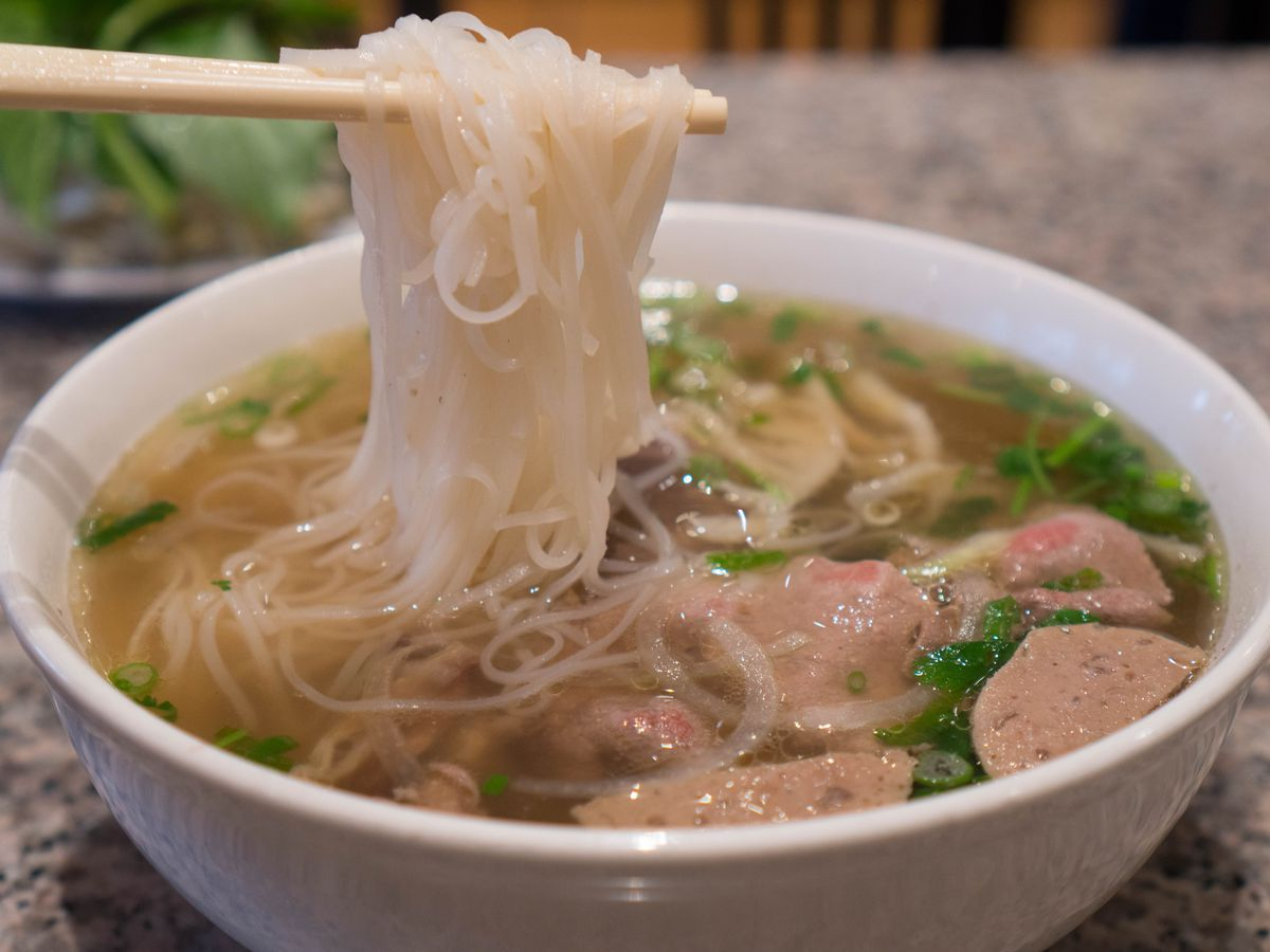 A pair of chopsticks hold up a tangle of noodles above a bowl of pho, with pieces of tripe and meatballs floating among chopped cilantro and basil