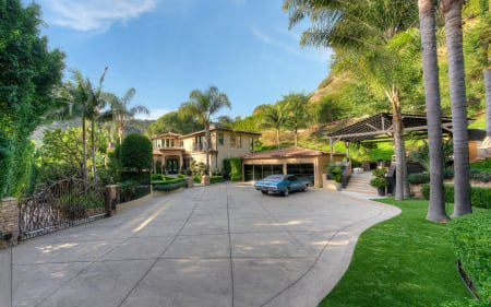A large driveway leading up to a garage and Spanish-style home.