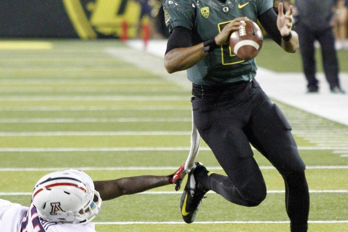 Oregon quarterback Marcus Mariota, right, avoids Arizona defender Sir Thomas Jackson as he looks for a receiver during the second half of their NCAA college football game in Eugene, Ore., Saturday, Sept. 22, 2012.   Mariota threw for 260 yards and two tou