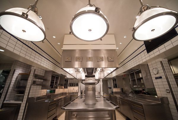 Per Se's kitchen has three lights up top, white brick, and stainless steel counters