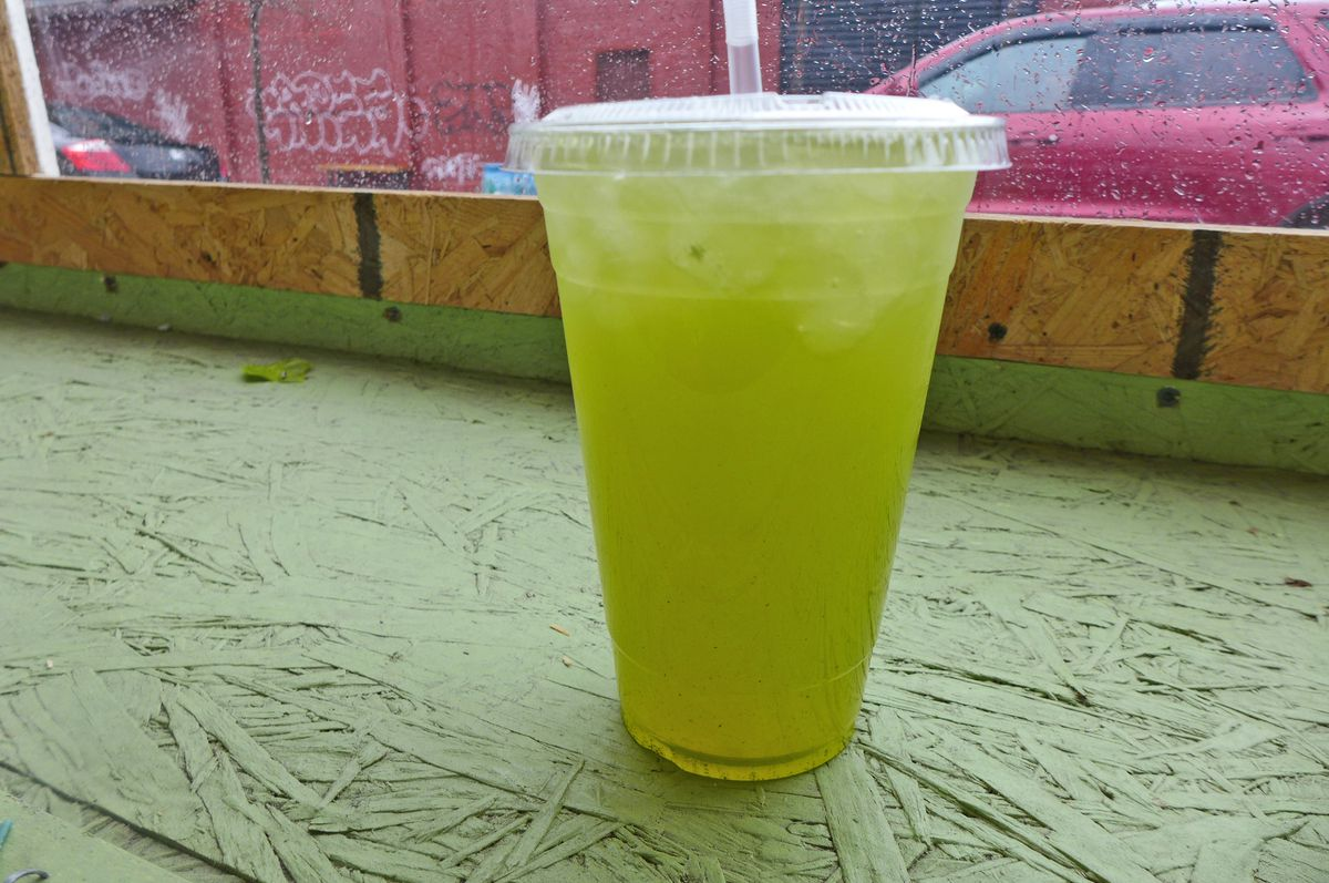 A plastic glass with a greenish fluid on a rough green counter.