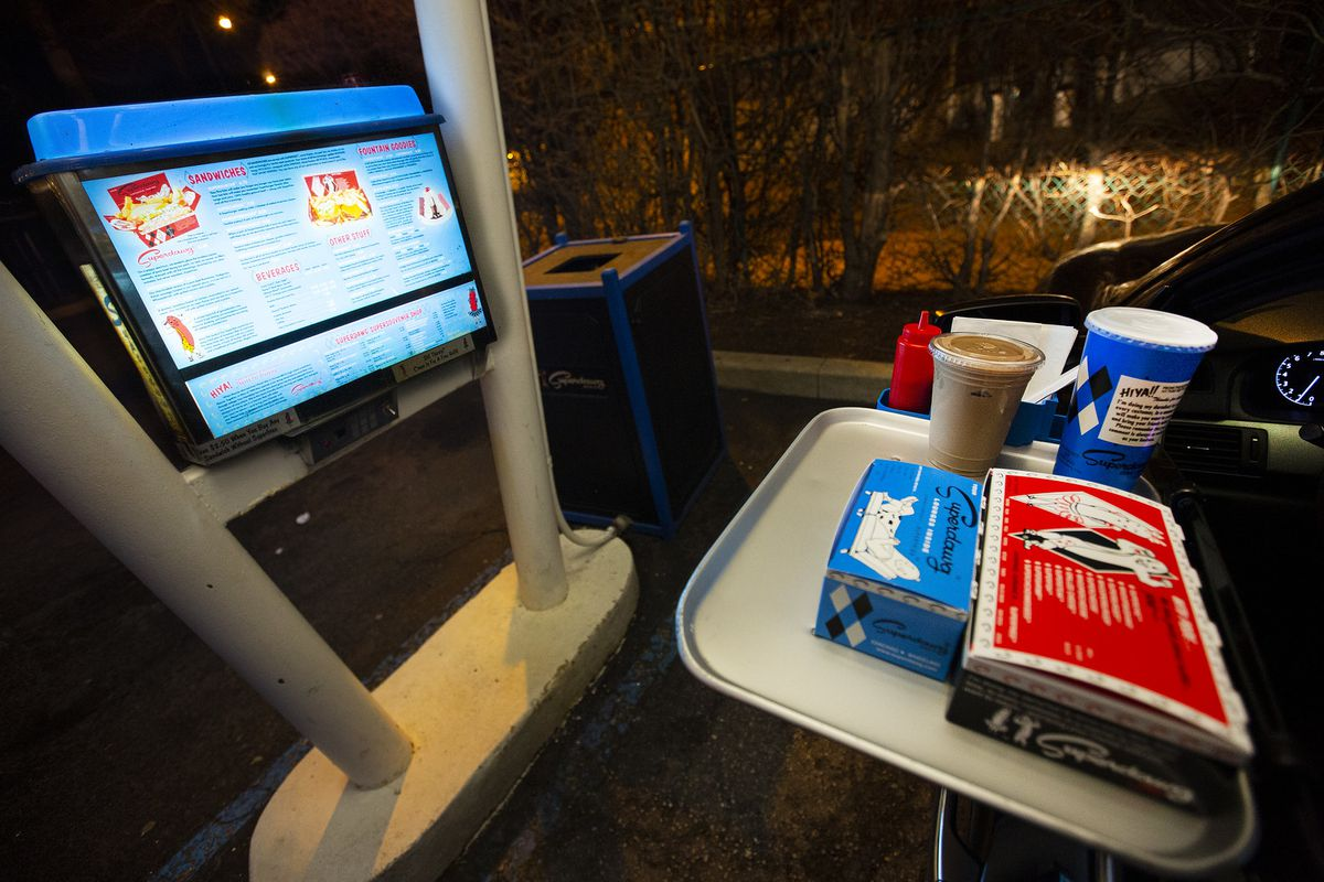 A carhop with tray of food hanging from a door and drive-in menu.