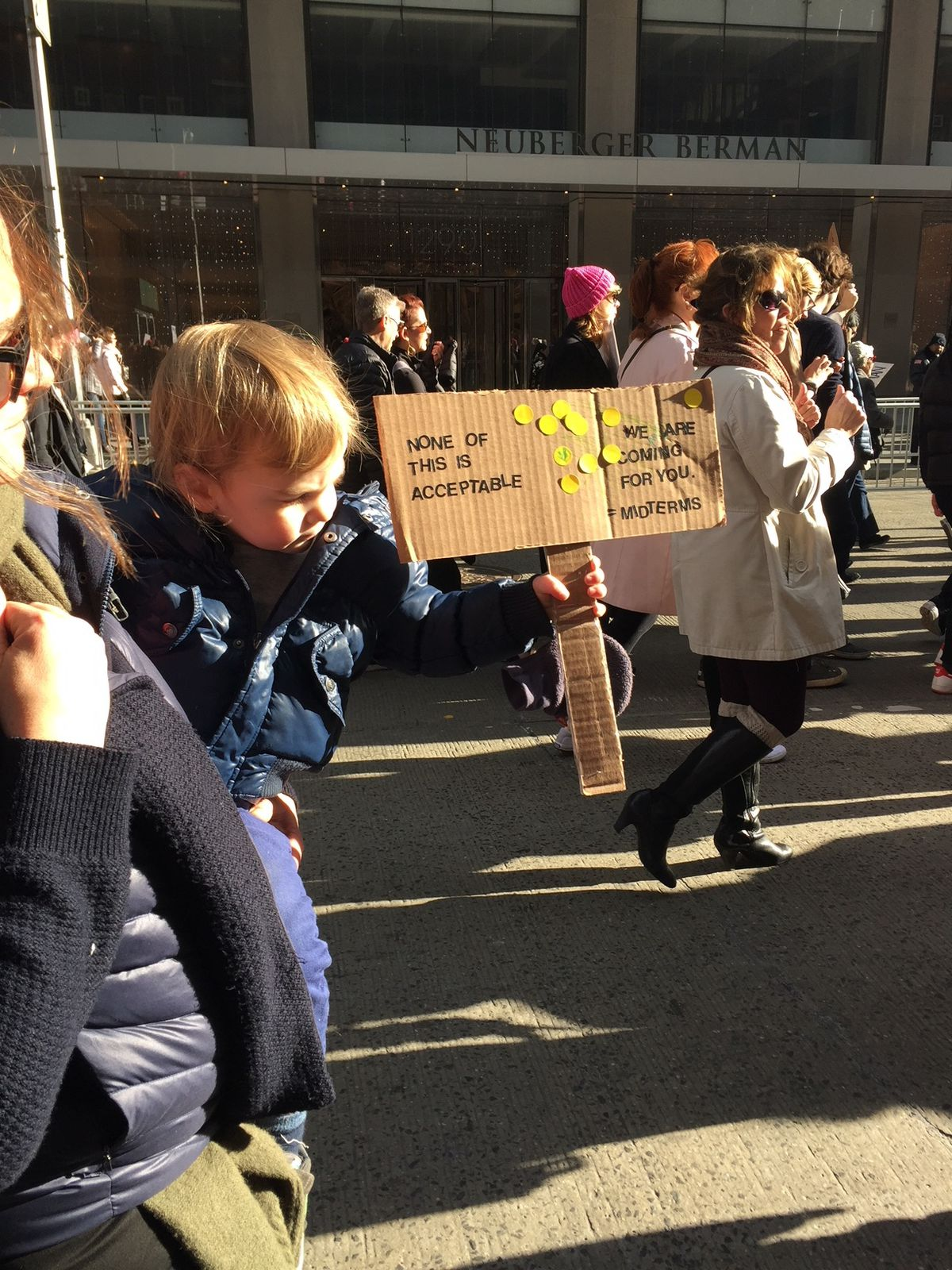 """A boy holding a sign reading """"None of this is acceptable"""" with yellow stickers"""