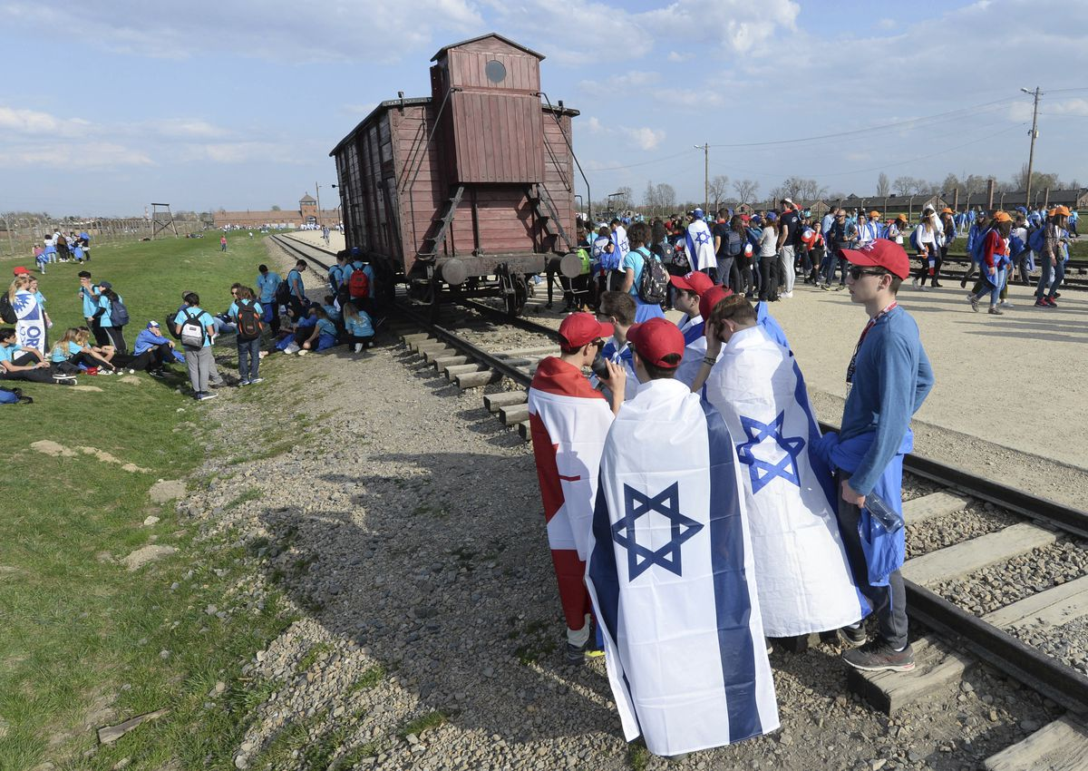 """People take part in the annual """"March of the Living"""" to commemorate the Holocaust by marching between the former death camps of Auschwitz and Birkenau, in Oswiecim, Poland earlier this month.   Associated Press"""