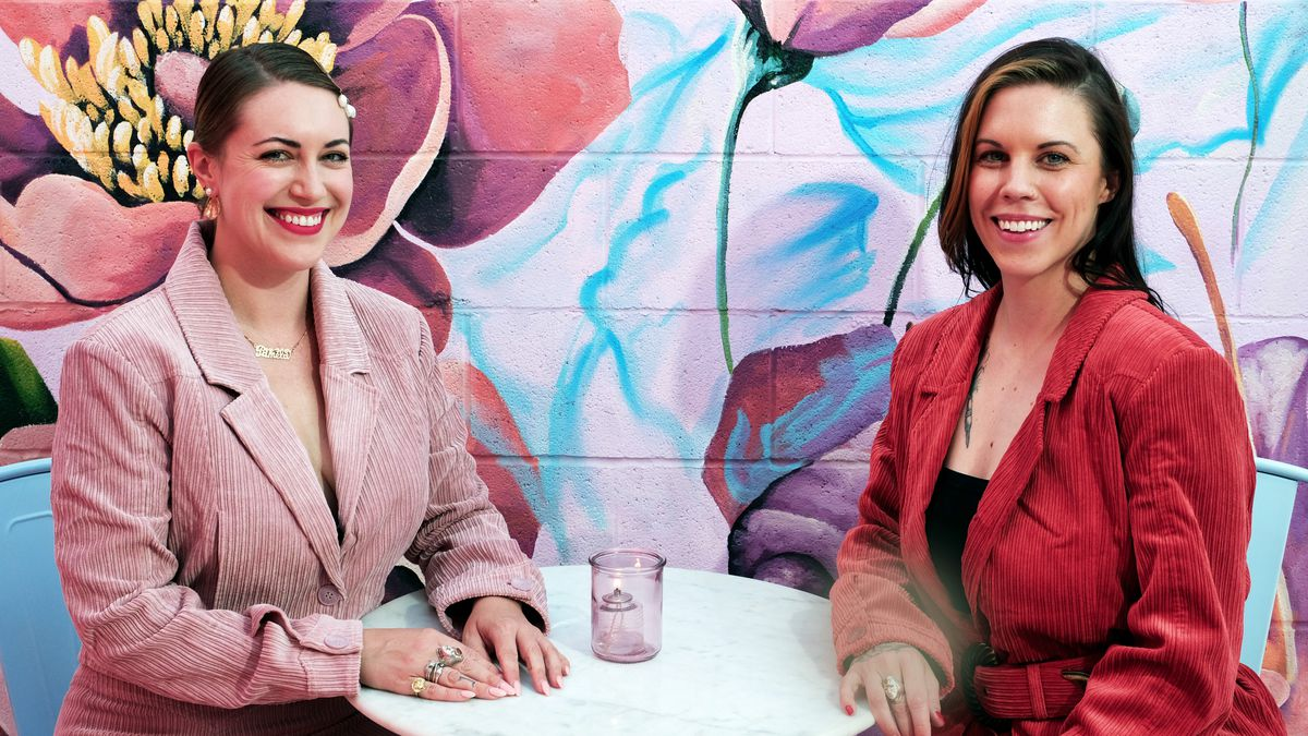 Two women, one in pink and the other in red, sit at a table in front of a mural.
