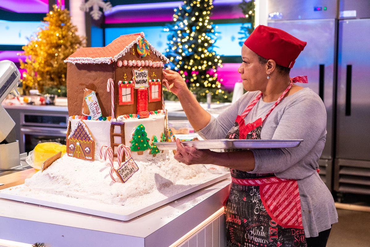 a woman decorates an elaborate gingerbread house