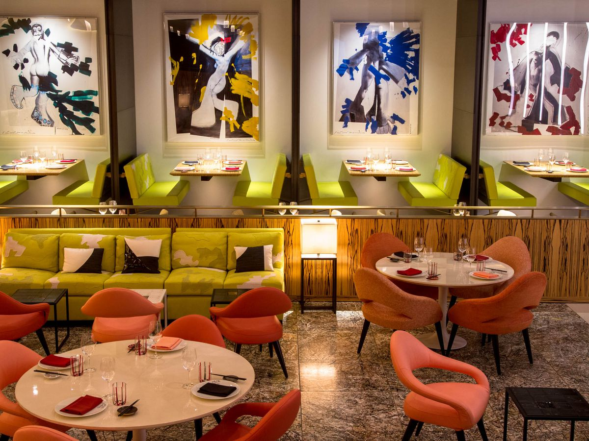 A colorful and cozy dining room with orange chairs, green booths, and abstract artwork on the wall