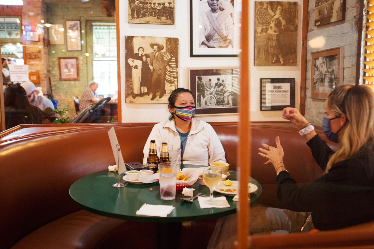 Diners still wear masks while seated at a table at South Congress restaurant Guero's