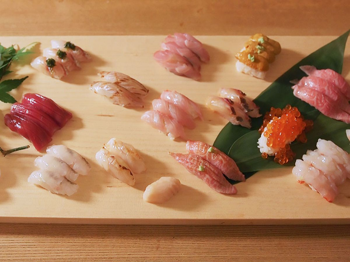 An overhead photograph of a platter of sushi arranged on a light wood cutting board, with leaves and other herbs