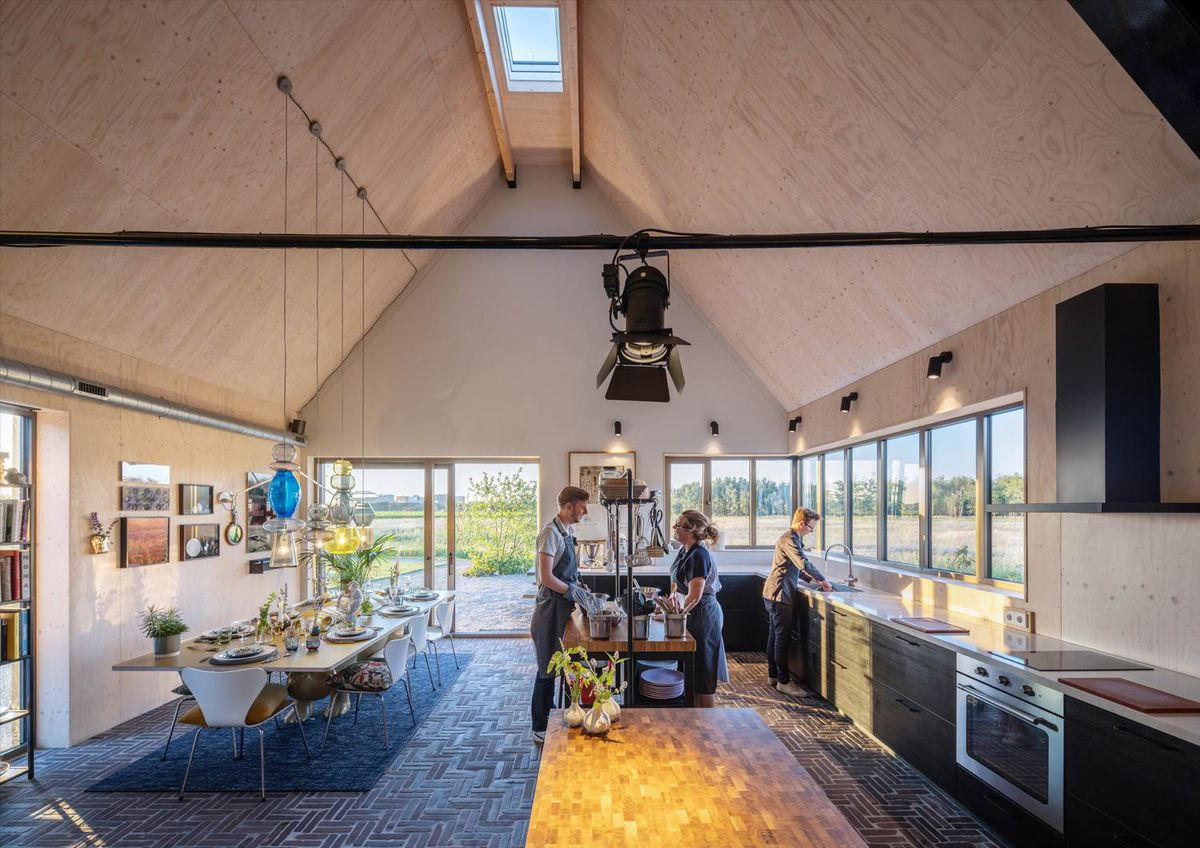 People cooking in a cooking studio under a gabled roof, with a dining room on the left and a kitchen on the right.