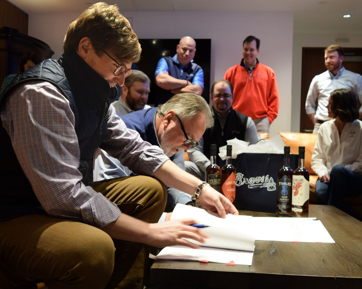 ASW Distillery co-founder Charlie Thompson signing the lease for a space at Battery Atlanta