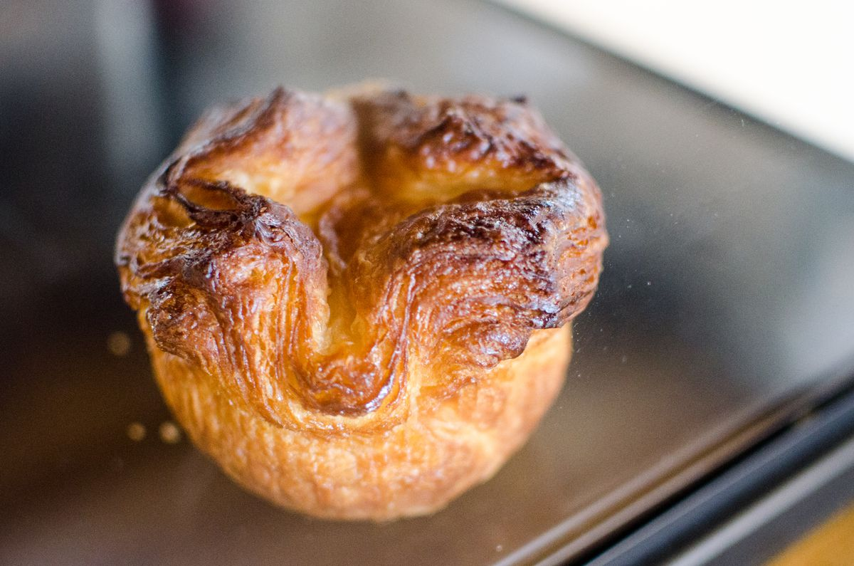 A single kouign-amann pastry sits on a shelf