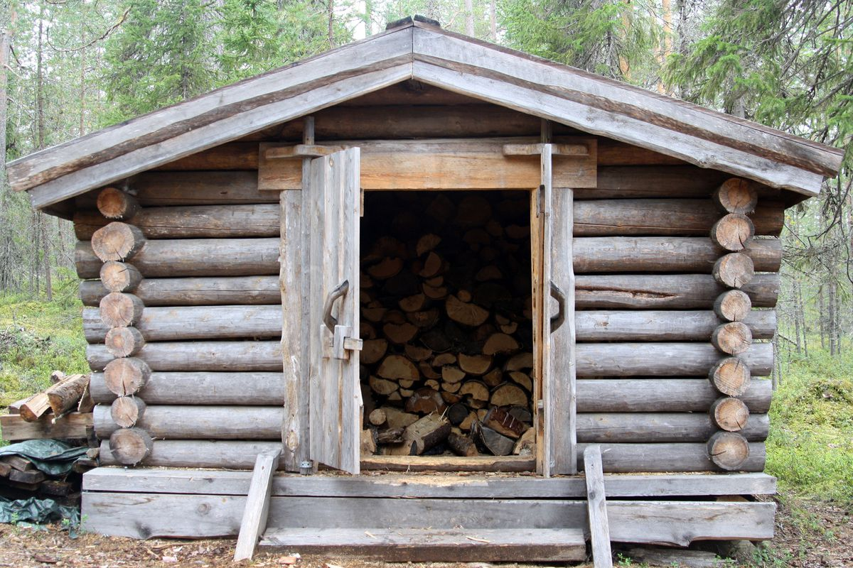An old log cabin shed repurposed to store firewood.