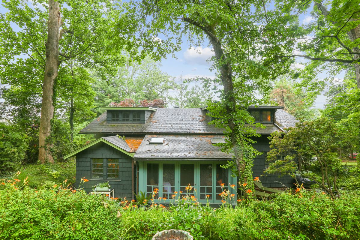 An exterior view of an Arts and Crafts style home that sits surrounded by green foliage.
