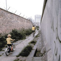 Father and son riding their bicycles along a section of the Berlin Wall, July 1981.