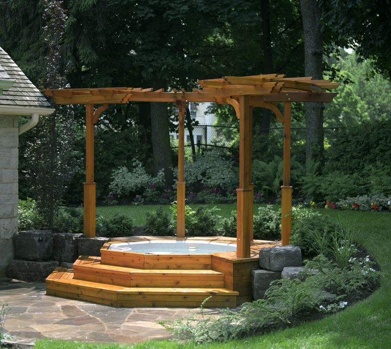 A backyard hot tub surrounded by tiered wooden steps and a matching pergola.