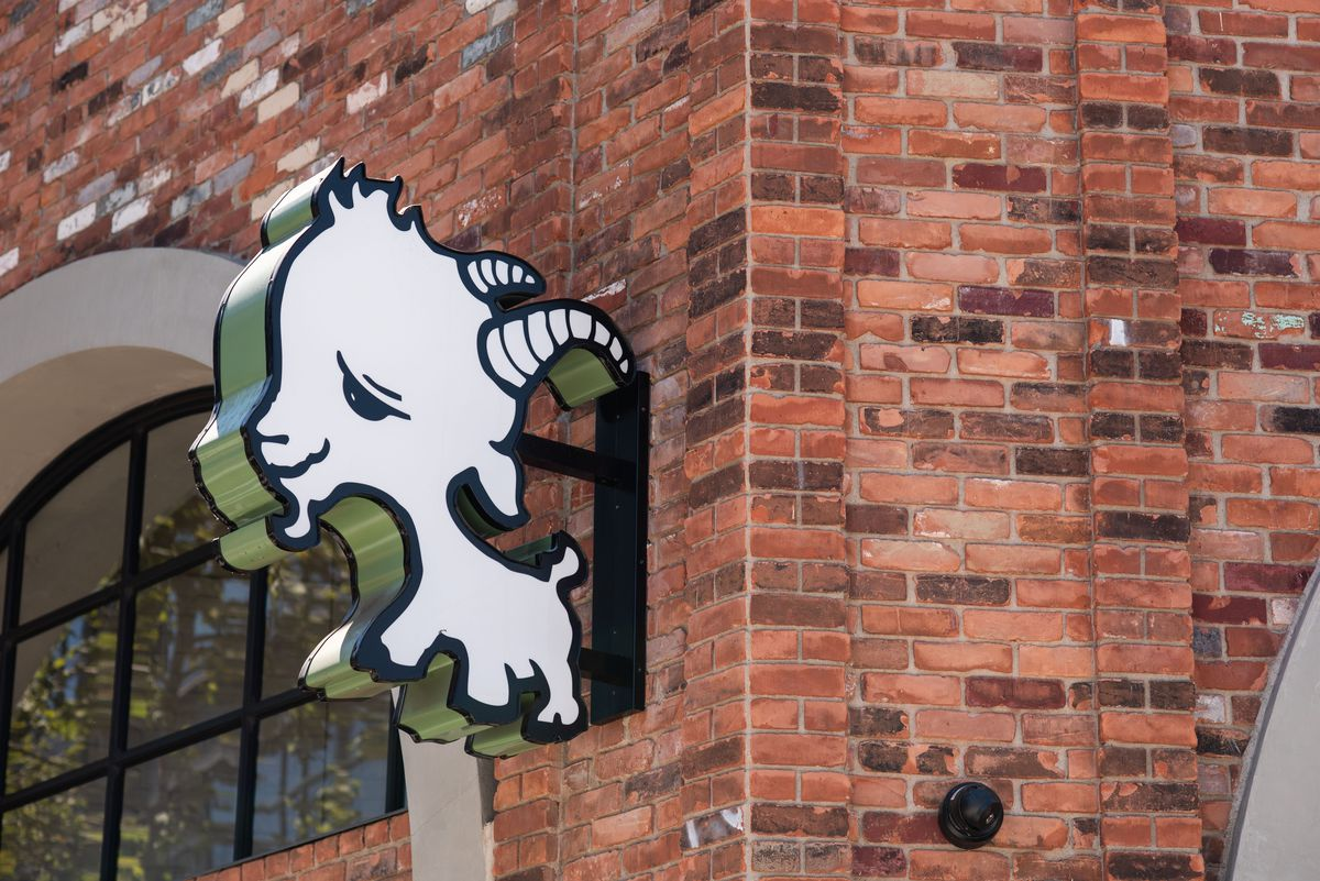 A smiling logo of a goat made into a dinnertime restaurant neon sign.