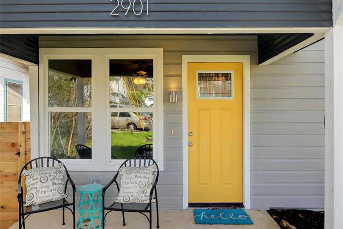 Medium shot of gray wood/hardiplank house with bright yellow door