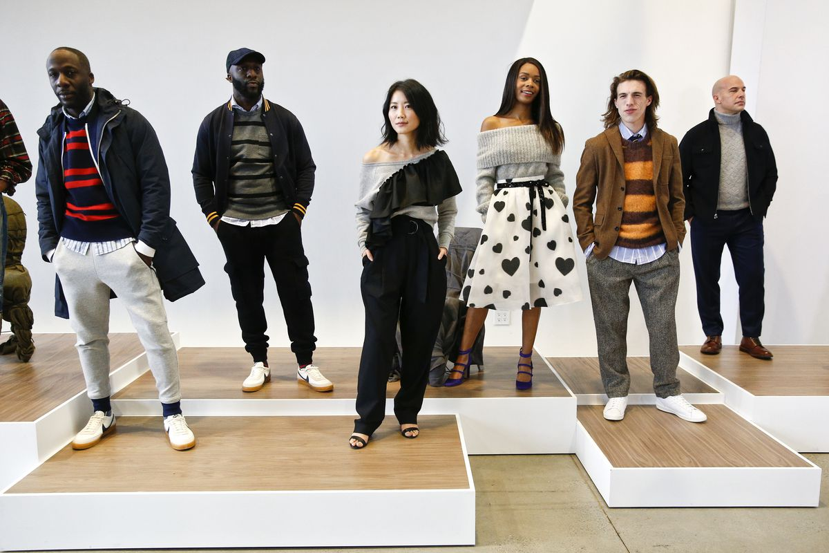 Models stand on a platform wearing J.Crew clothing.