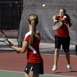 As her sister Arie looks on, Amanda Naylor of Manti makes a return against Katie Panushka and Kelsey Almony of St. Joseph (not pictured) in the State 2A Tennis first seed doubles tournament at Liberty Park in Salt Lake City Saturday, Sept. 29, 2012.