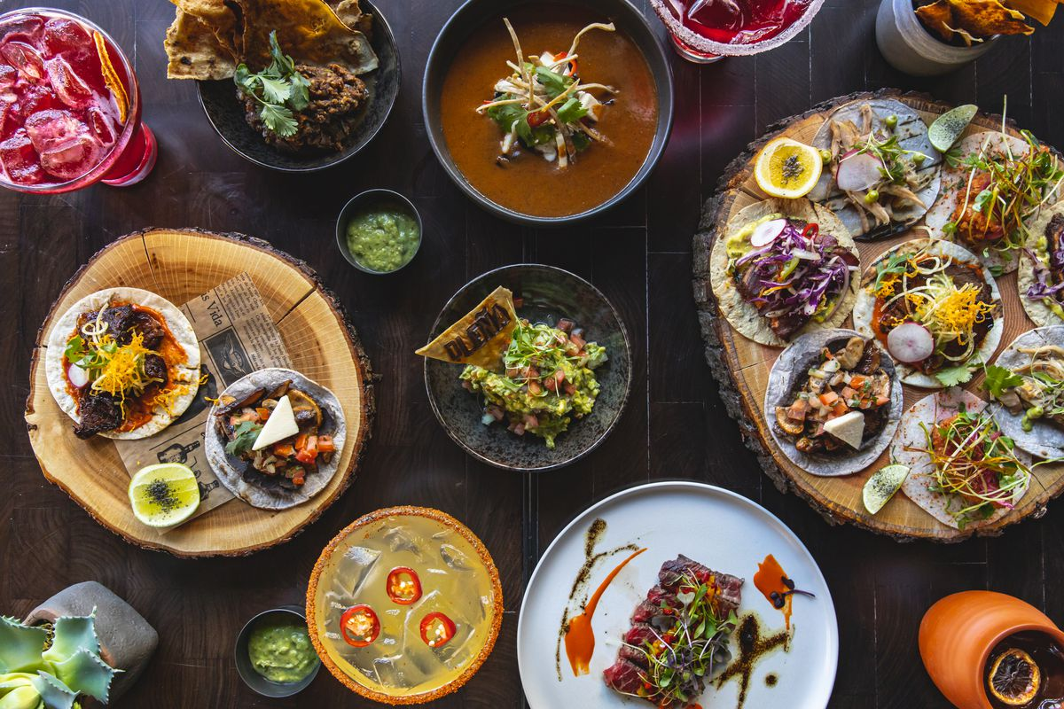 A variety of tacos presented on a tree stump platter, and other dishes from DLeña