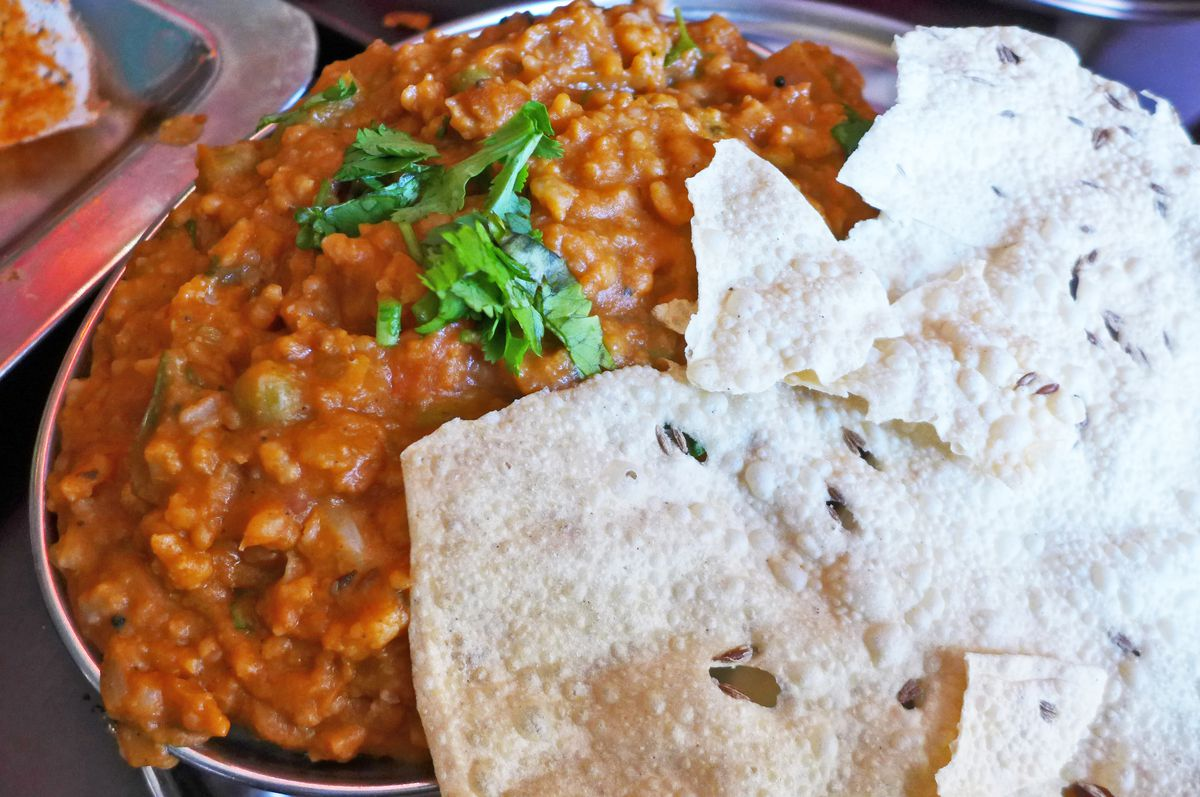 A thick red stew of minced vegetables with a big round cracker laid across the top.