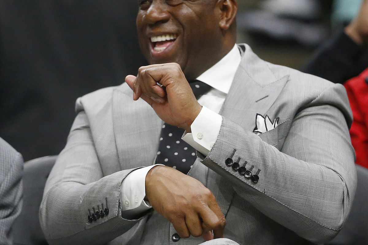 """Former Los Angeles Lakers player Earvin """"Magic"""" Johnson laughs as he sits court side during the second half of an NBA basketball game between Atlanta Hawks and Los Angeles Lakers Tuesday, Feb. 12, 2019, in Atlanta. The Hawks won 117-113. (AP Photo/John Ba"""