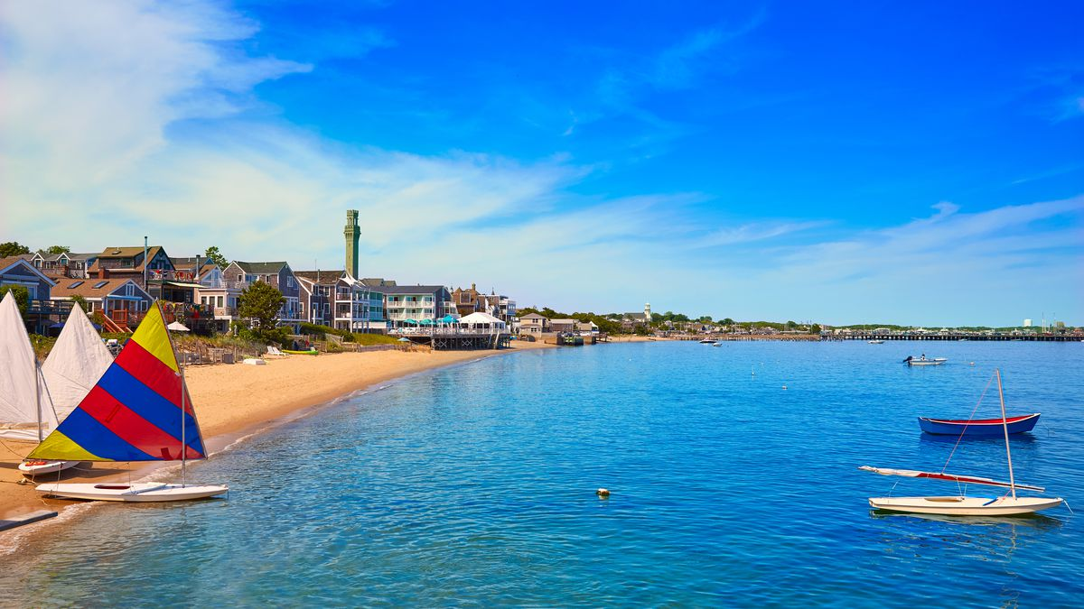 Blue water and a strip of beach in Provincetown, Cape Cod, Massachusetts. Houses line the beach, and sailboats with colorful sails are next to the water.