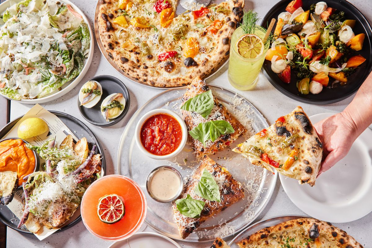A table full of pizza, salads, and cocktails from Fiorella Sunset