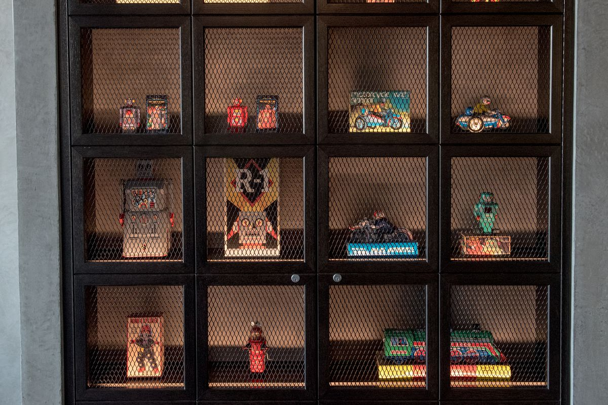 A closeup of a shelf filled with Japanese toy robots and other knick-knacks, behind a cage.