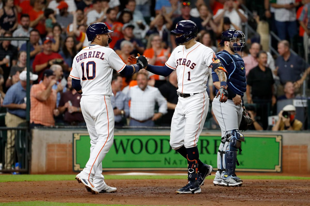 Yuli Gurriel #10 of the Houston Astros congratulates Carlos Correa #1 after a three run home run in the fourth inning against the Tampa Bay Rays at Minute Maid Park on September 30, 2021 in Houston, Texas.