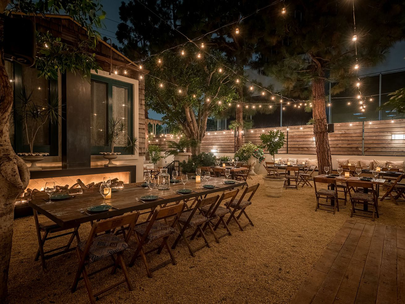 A dark patio with string lights, rocky ground, and a wooden table.