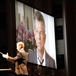 Video of musical composer David Foster expressing his thoughts about the joy of music is displayed on giant screen as associate music director Ryan Murphy conducts Mormon Tabernacle Choir and Orchestra at Temple Square during dress rehearsal July 19, 2012 for Pioneer Day Concert.
