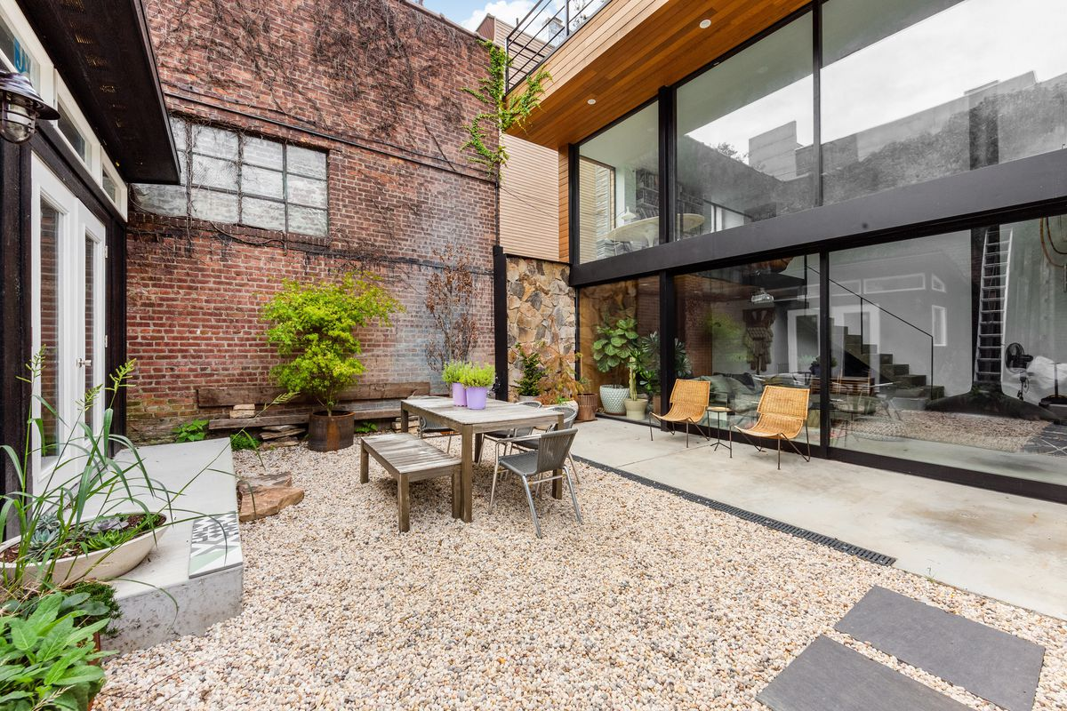 A patio outside of a house with stone pavings, a brick and stone wall, and a table and chairs.