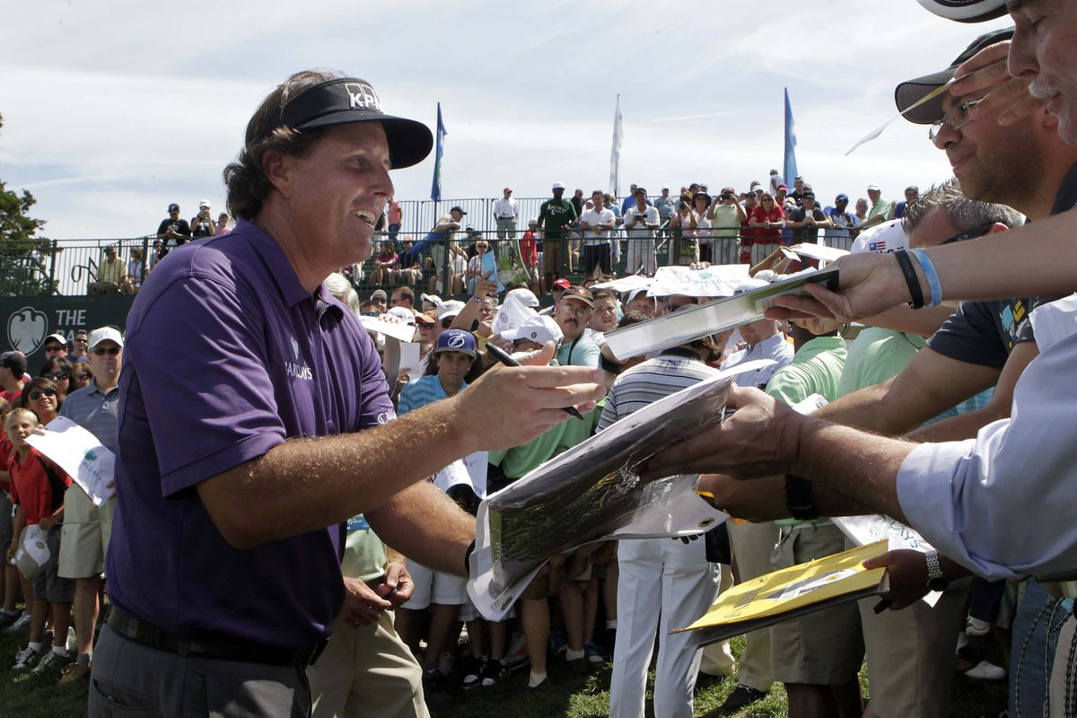 Aug 21, 2012; Farmingdale, NY, USA; Phil Mickelson (USA) signs autographs during a practice round for The Barclays at Bethpage State Park.  Mandatory Credit: Tim Farrell/THE STAR-LEDGER via US PRESSWIRE
