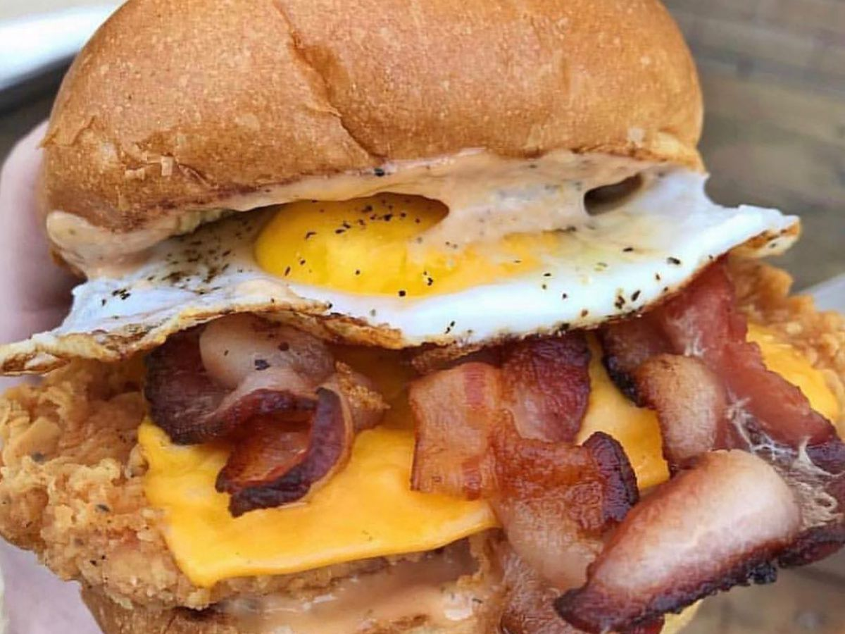 A fried chicken sandwich with bacon and a fried egg