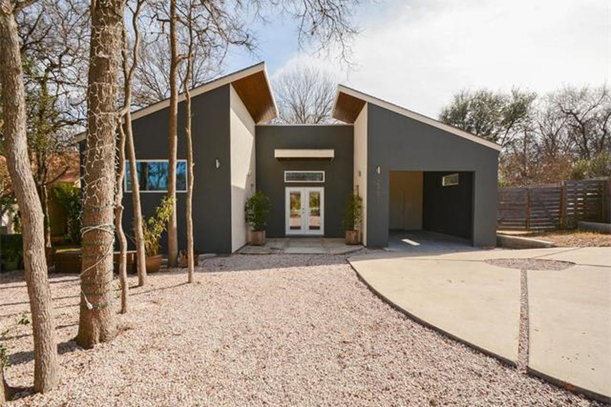 Contemporary recent build with two angled-roof structures (garage and house) connected by a recessed, flat-roofed entry, stucco, gray with white trim, big trees and lot, large gravel walkway