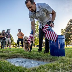 Volunteer Jeff Weber places flags while his dog Nike watches at Larkin Sunset Gardens Cemetery in Sandy on Thursday, May 27, 2021. More than 200 youth volunteers from around the Salt Lake Valley honored military veterans for Memorial Day by placing 3,000 American flags on the graves of service members. In addition, they swept and polished headstones and helped beautify cemetery grounds.