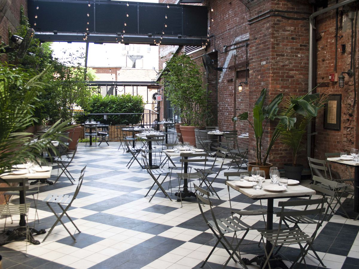 Tables and chairs set up outside on a black and white tiled patio with plenty of greenery surrounding the tables.