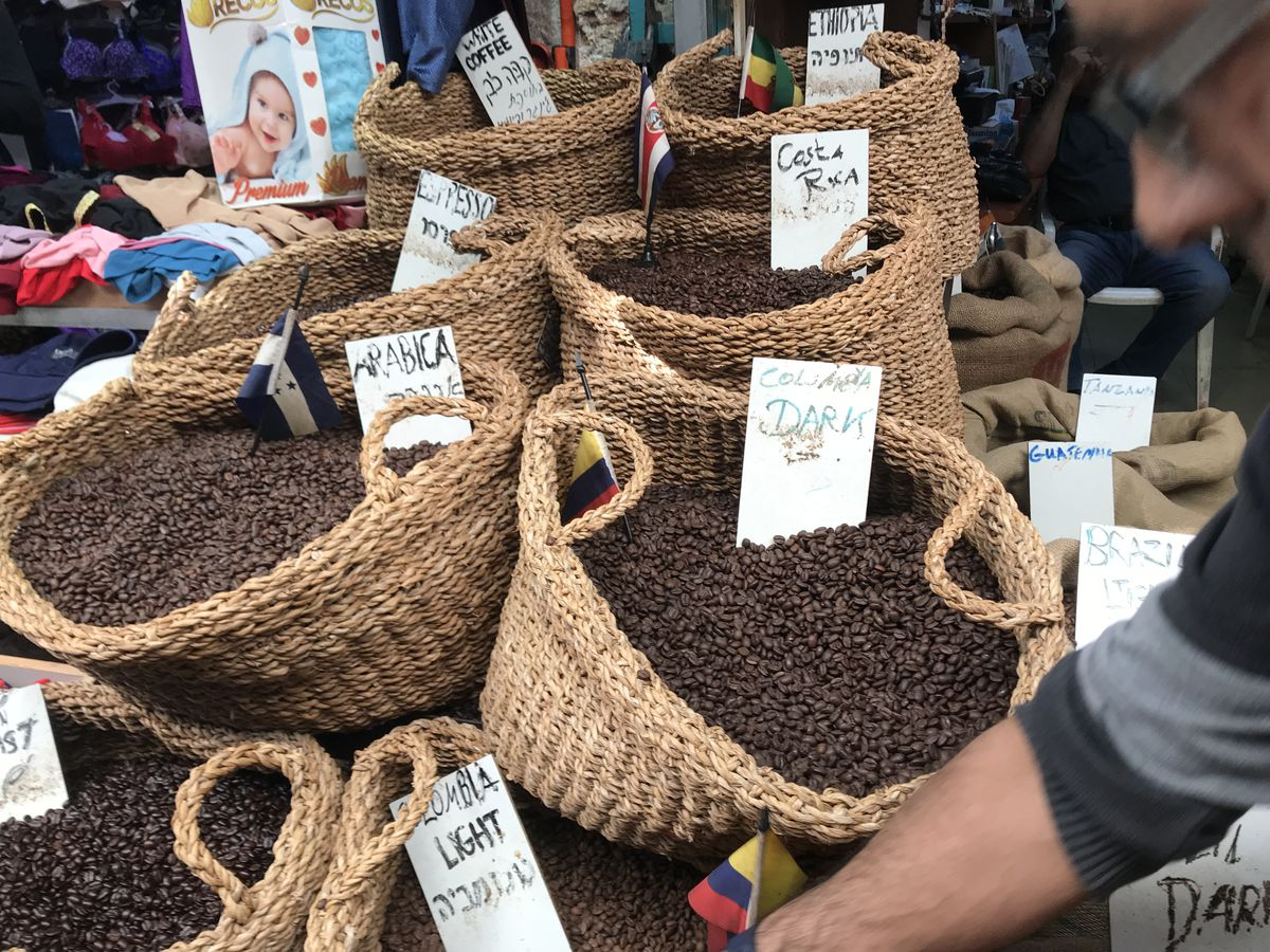 Woven baskets full of coffee beans with hand written signs stuck in each one listing where the beans come from as a man reaches in from the side of the picture