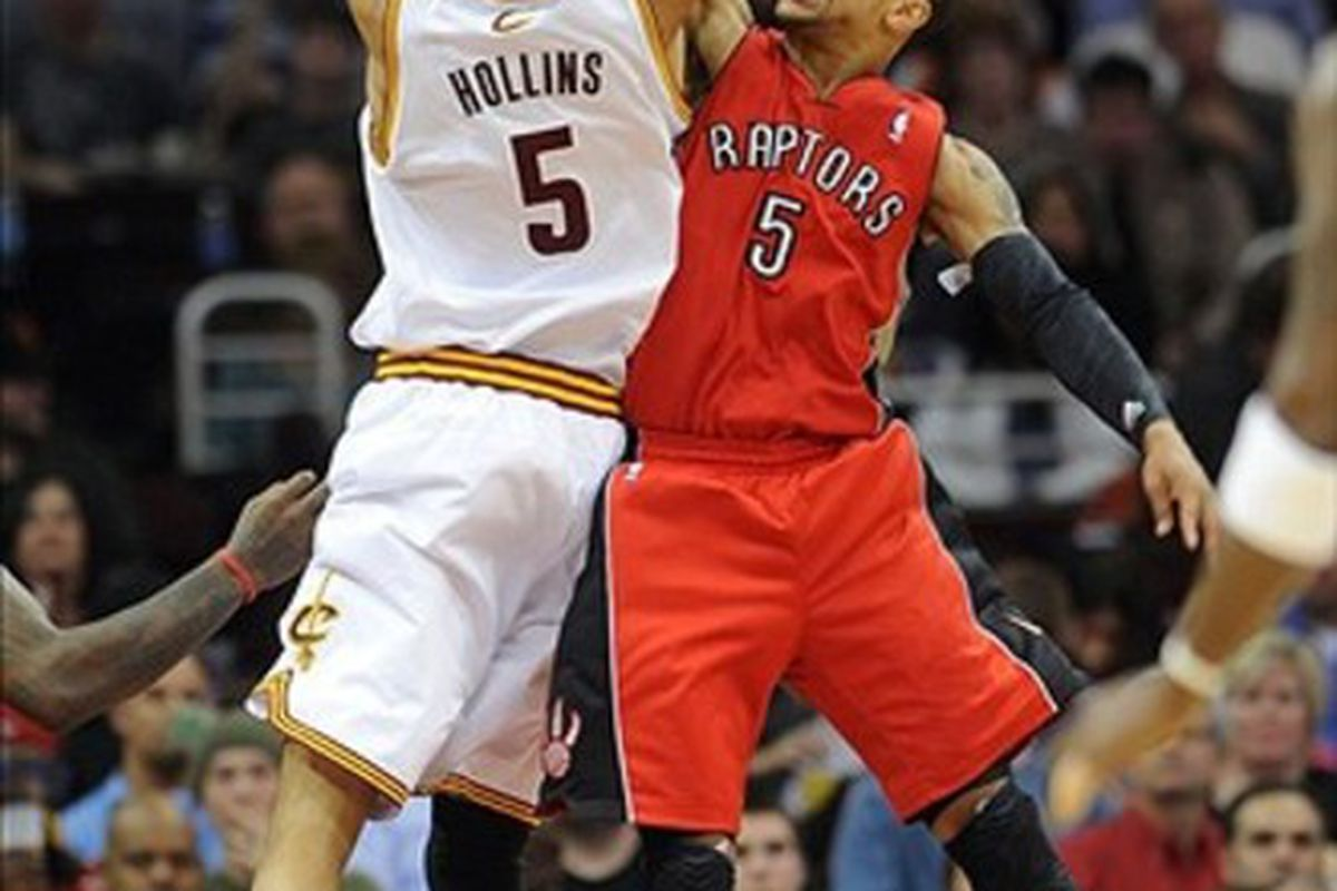 March 13, 2012; Cleveland, OH, USA: Toronto Raptors point guard Jerryd Bayless (5) blocks the shot of Cleveland Cavaliers center Ryan Hollins (5) during the game at Quicken Loans Arena.  Mandatory Credit: Eric P. Mull-USPRESSWIRE
