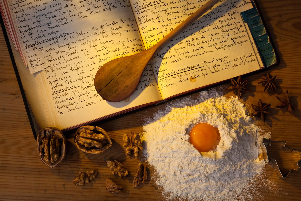 An open hand-written cookbook and a mound of flour with an egg yolk for making pasta.