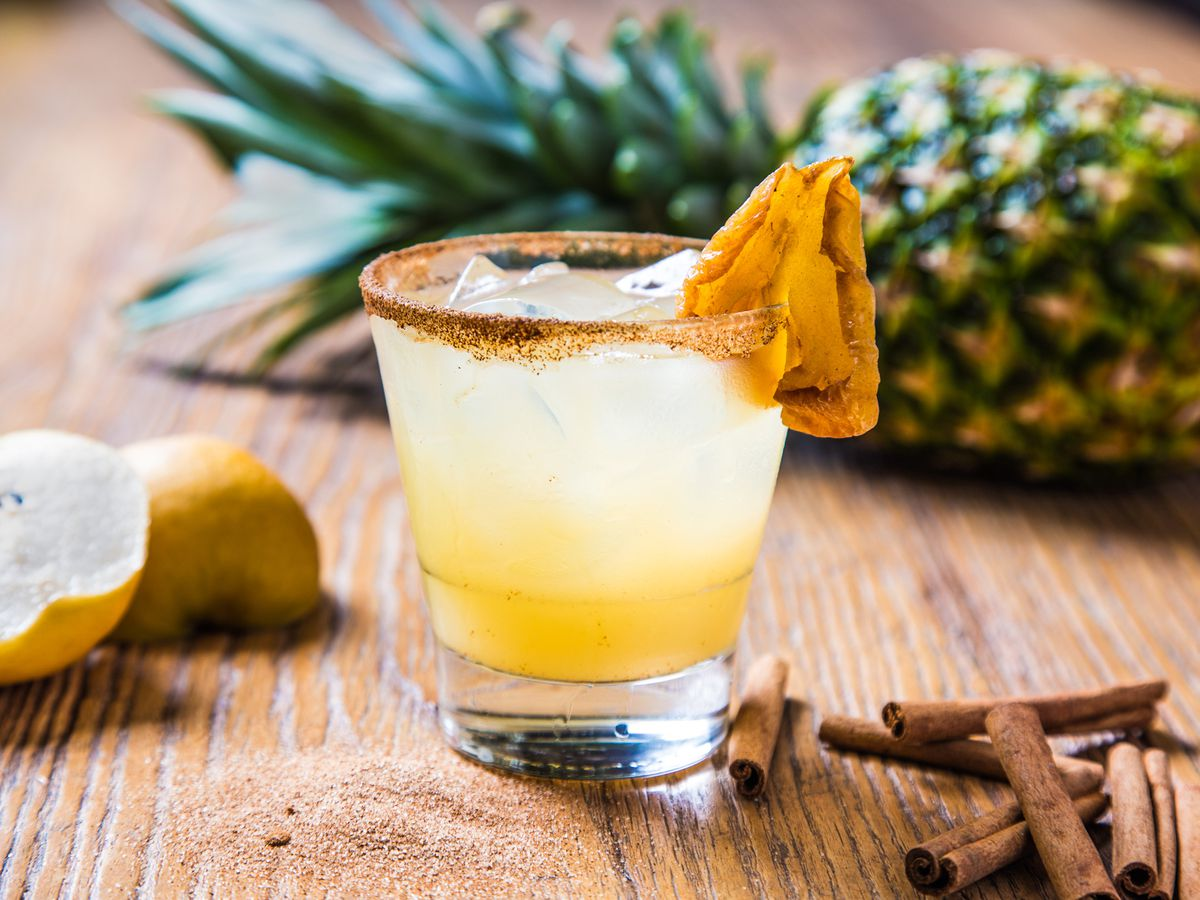 A short clear glass containing a yellow-colored cocktail garnished with a piece of dried pineapple.